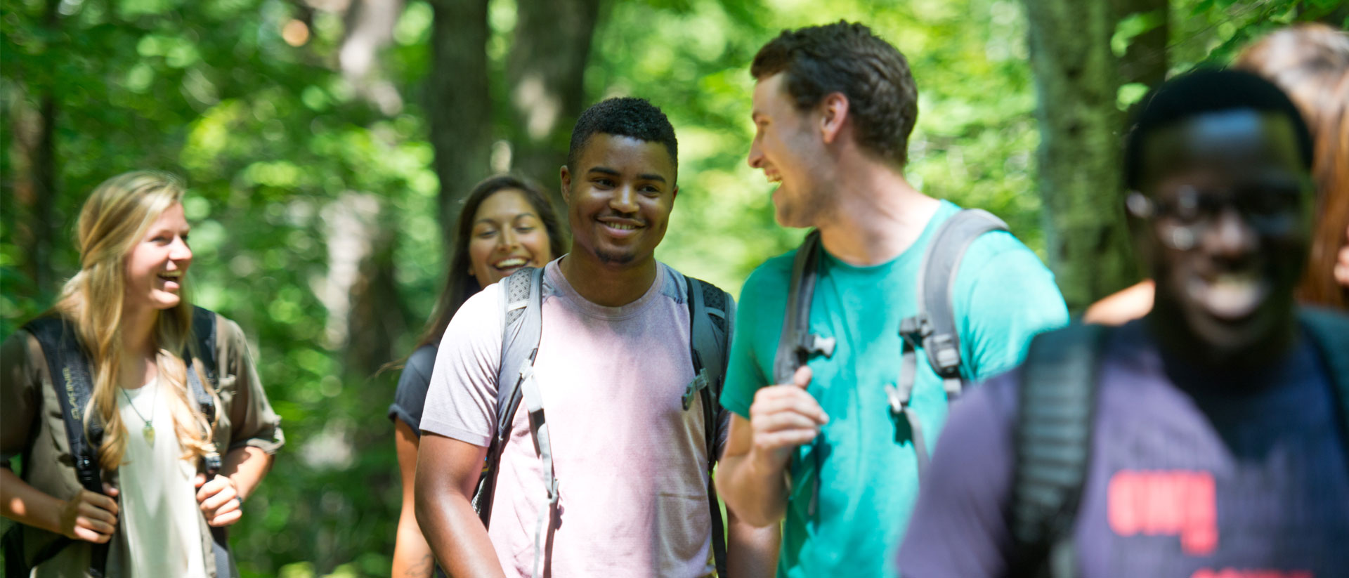Students gather in a wooded area, smiling and laughing.