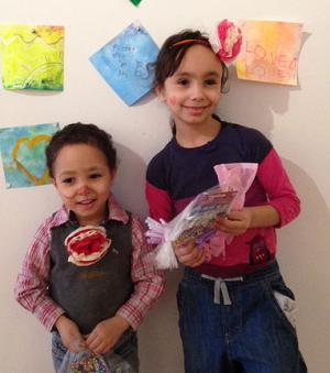 Children hold bags of art supplies