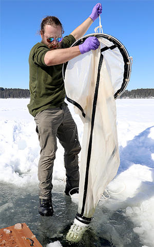 Ted Ozersky, a UMN Duluth assistant professor of biology, samples winter populations of zooplankton (tiny animals that eat algae and in turn are eaten by fish).