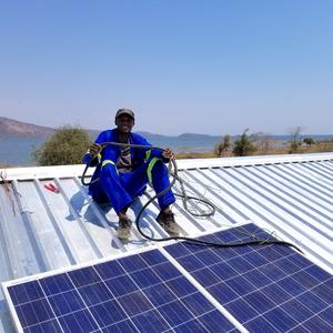 A worker in Mundulundulu Village, Siavonga, Zambia helps install a solar system.