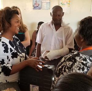 Muzalema Mwanza (left) brings a solar suitcase to a health clinic.