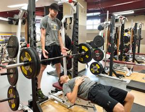 Dominic Toninato and Carson Soucy lift weights in the Bulldog's locker room
