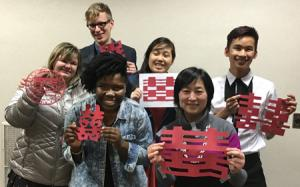 "Playing with scissors is part of the language class. The group cut out the figure ""double happiness"" in honor of the Chinese Year of the Monkey.  Back row (left to right): Stephanie Zanmiller, Calvin Miner, Mai Che Lee, and Devon Diaz. In front are Sharon"