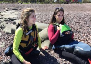 Two UMD female student lying on the beach