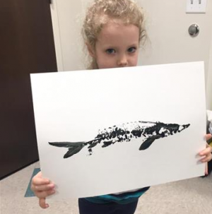 A girl holds up a print she made of a young sturgeon through a process known as Gyotaku. She participated in an event held last February for the Sturgeon Spectacular in Fond du Lac, Wisconsin.  Credit: Ryuta Nakajima