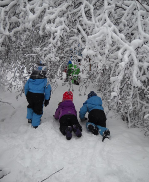 Three children crawl in the snow.