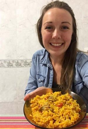 Abby with a plate of paella made by her host mother.