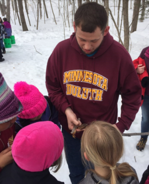 AISES student Aaron Moller showing students how a maple tap was made (photo credit: Marne Kaeske)