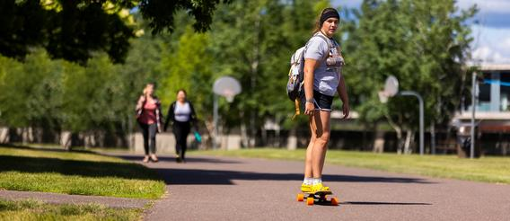 A student skateboarding past two other students on a college campus.