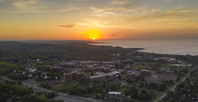 A drone shot of sunrise over Lake Superior and the UMD campus.