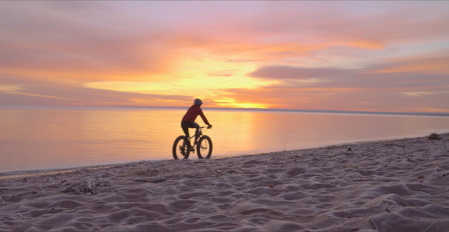 A person riding a bike at sunrise along the shore of Lake Superior.