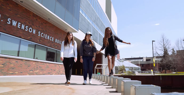 Three female students walking outside Swenson College of Science and Engineering