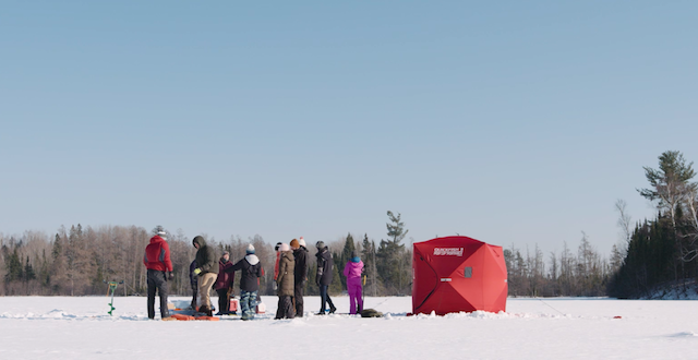 Students standing on a frozen lake next to a red tent.