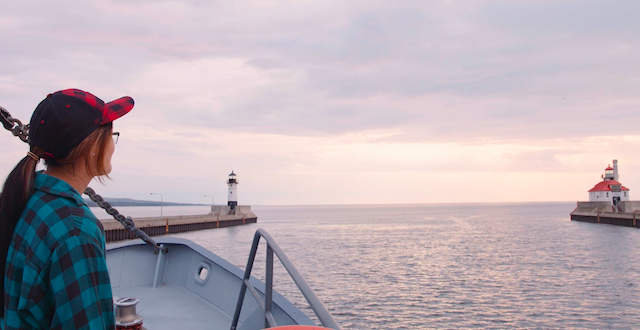 A student on board a boat, looking out at the Duluth harbor.