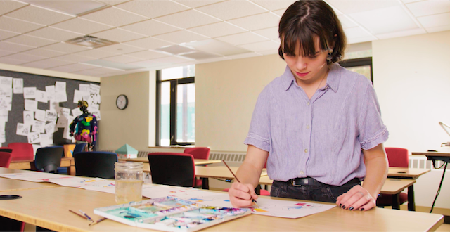 A student painting on a large piece of white paper in a classroom.