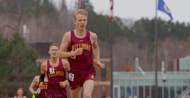 Three students in maroon and gold track uniforms, running on a track.