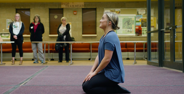 A woman with blonde hair sitting on the floor on her knees, smiling and looking upward. Several people in the background are watching her.