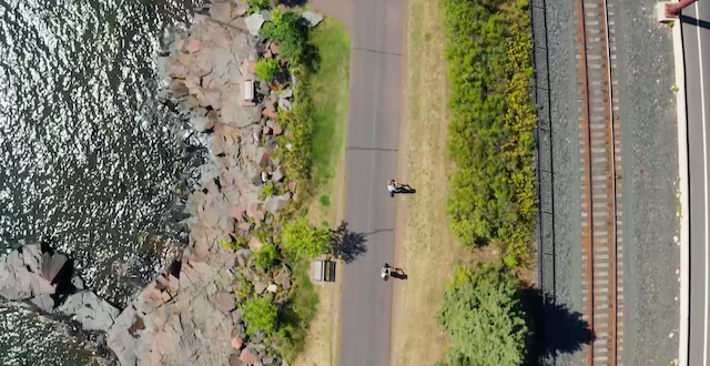 A drone shot of two people riding scooters on a path next to Lake Superior.