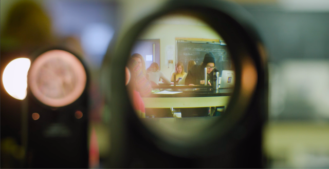 A student in a physics classroom, seen through a photometer.