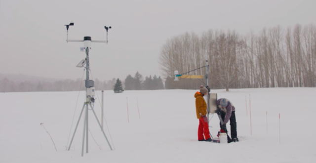 Two students standing on a frozen lake with scientific equipment.