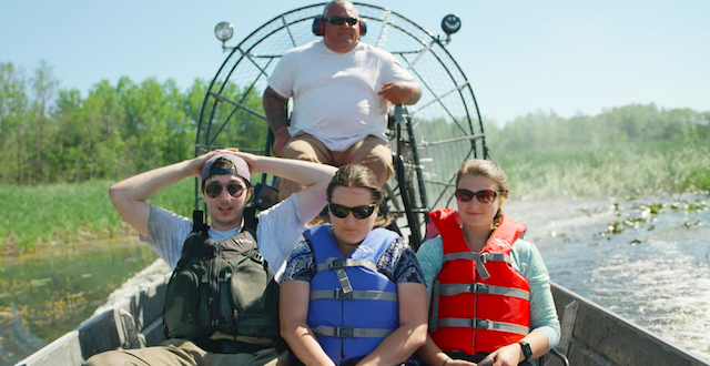 Three students and a faculty member in a boat, in a swamp