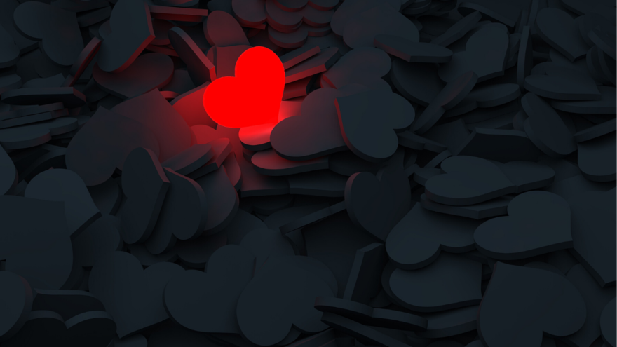 Stock photo of one red heart surrounded by all black hearts