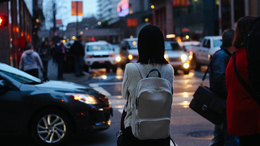 Young person seen from behind waiting to cross a busy street at twilight