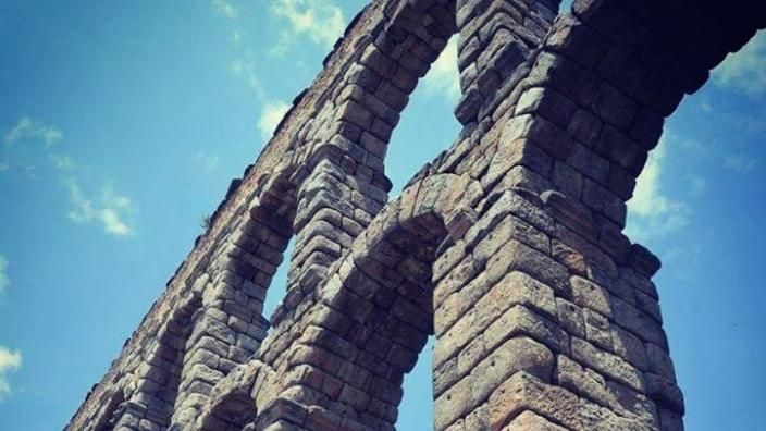 a close-up of the Aqueduct of Segovia stone arches