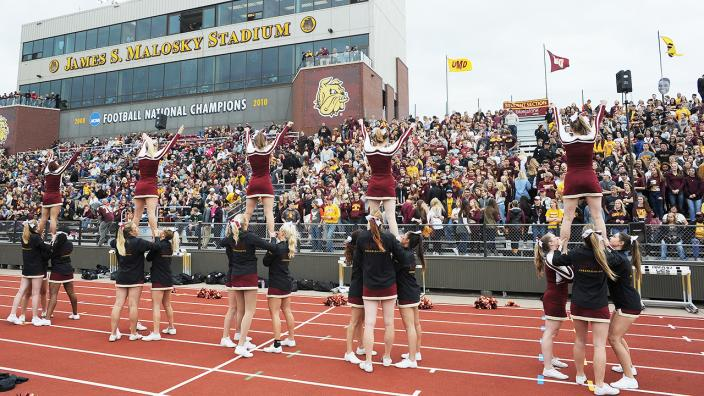 Cheerleaders and the crowd at a UMD Homecoming football game