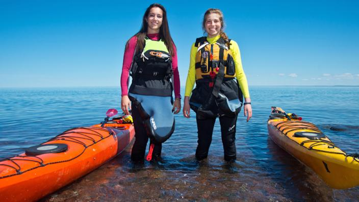 Lexi and Erin suit up and wade in Lake Superior with their kayaks