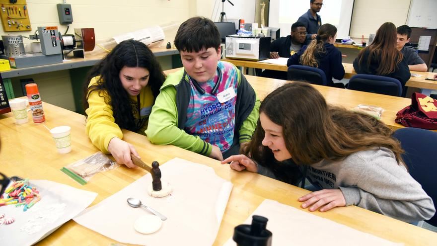 Female UMD student working with two school kids on an experiment