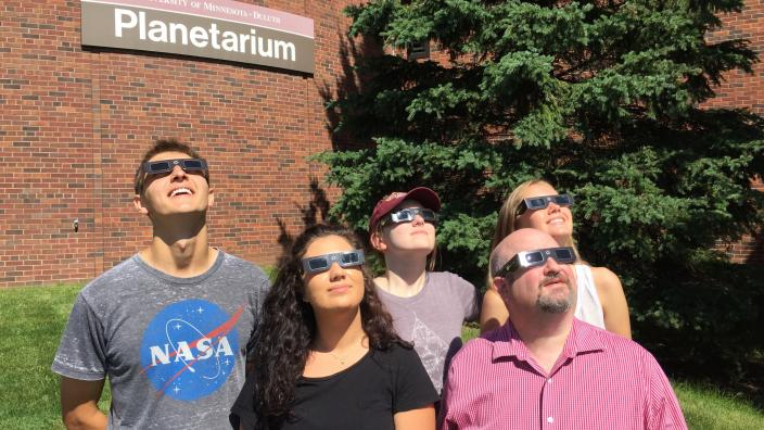 A group of UMD students and faculty view the sun with solar eclipse glasses.