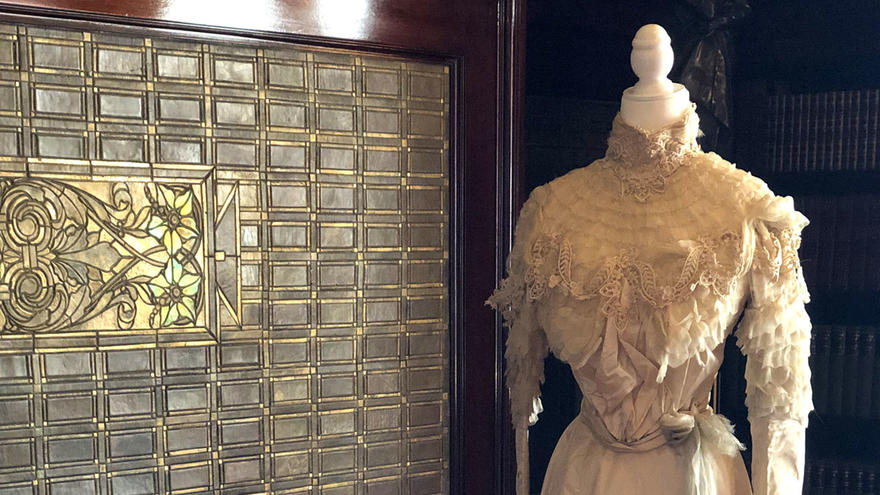 Ivory colored gown on a mannequin in front of a Glensheen fireplace