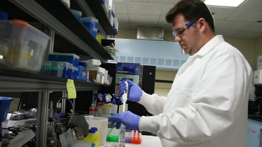 Man in lab coat syringing a liquid into a test tube.