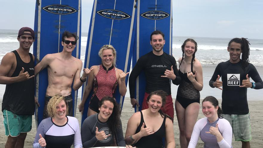 Ten UMD study abroad students posing on a beach with their surf boards