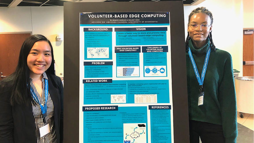Two female UMD students flanking a research poster.