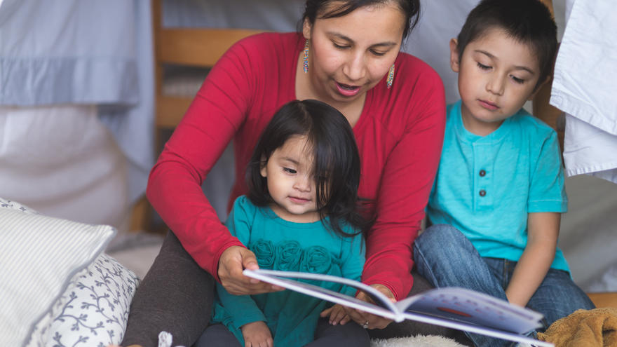 American Indian woman reading to a young boy and girl