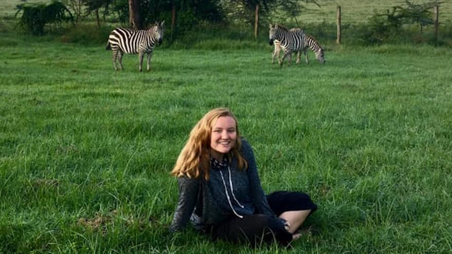 Katie Desautels sitting on grass with two zebras in the background