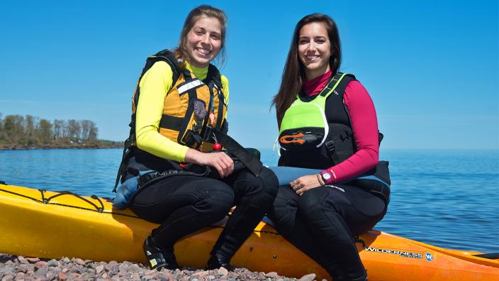 UMD alumna who paddled around Lake Superior sit by their kayaks on the shoreline