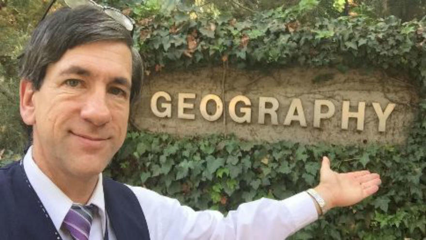 """UMD Professor David Syring in front of a sign that says """"Geography"""""""