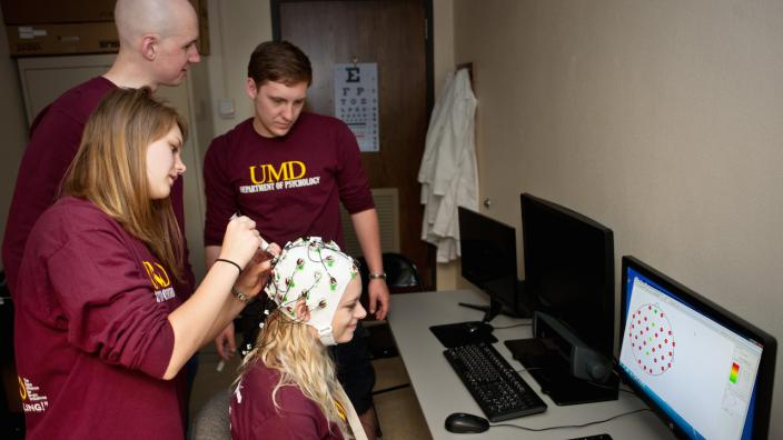 Psychology students practice a demonstration that illustrates brain concepts.