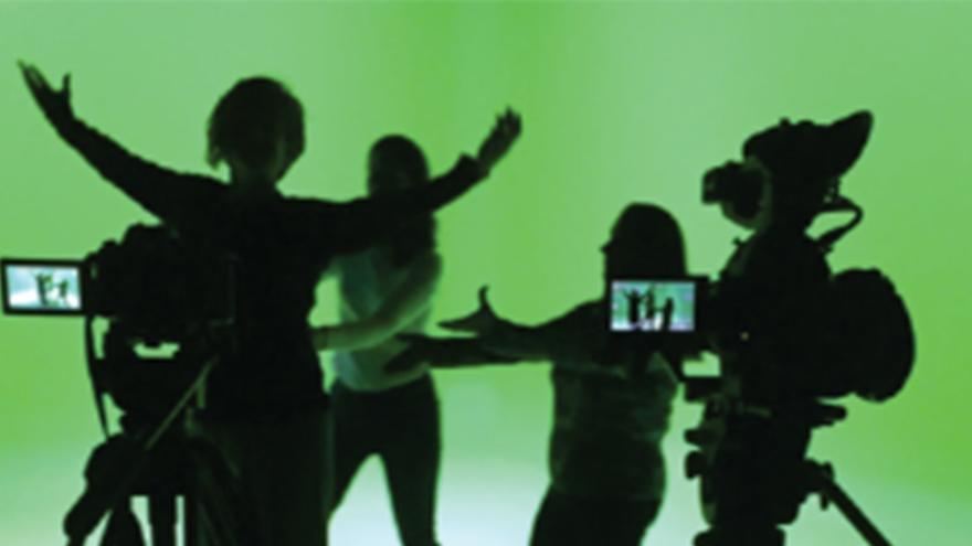 Silhouettes of people in front of green screen