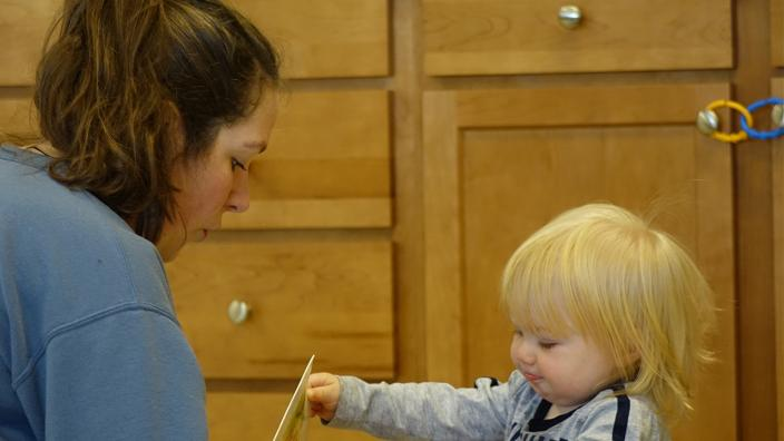 A female UMD student working with a toddler who lives in the Steve O' Neil apartments
