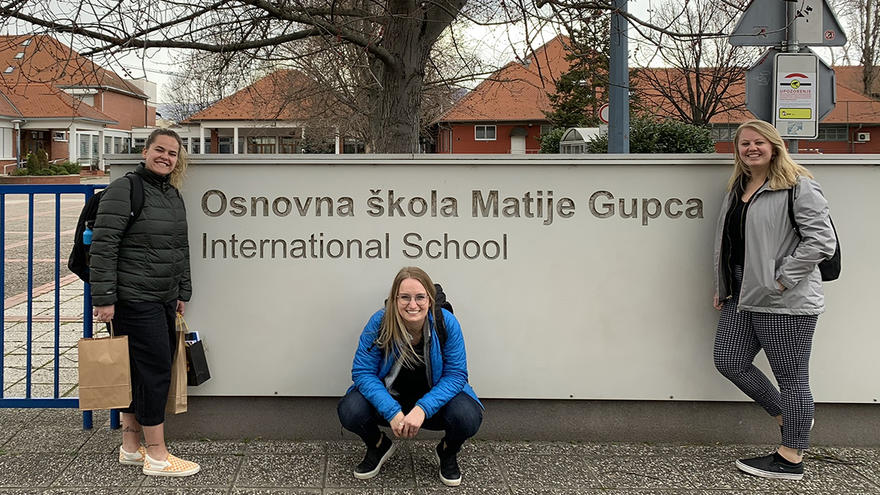 UMD Education students Cass Welhouse, Alexia Bjerke, and Megan Blaszkowski, in front of Croatian international school sign.