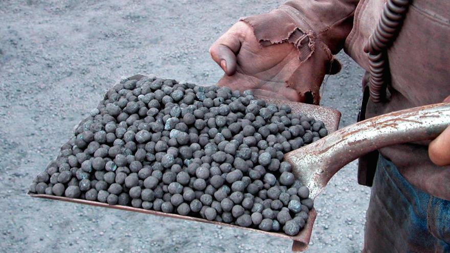 Hands holding a shovel of taconite