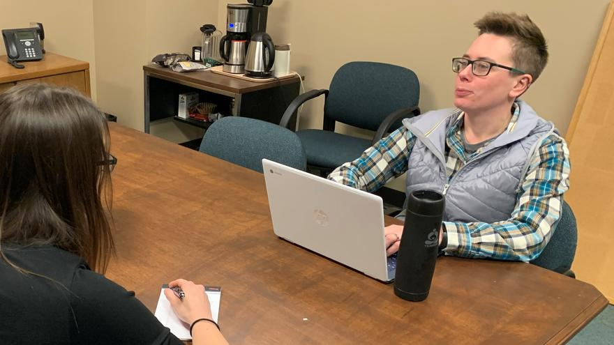 Tiffany Sprague sitting on the table with her laptop being interviewed by a student