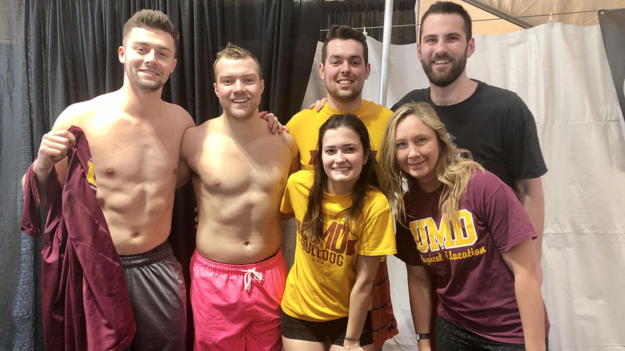 Members of the student club UMDUnified standing in swimwear smiling at camera