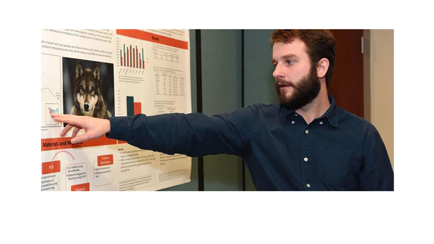 UMD student pointing at a poster