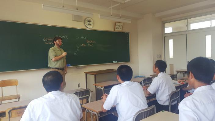 UMD Alumnus Zach Lunderberg standing before his class in Japan.