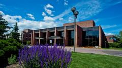 The exterior of the Marshall Performing Arts Center with purple flowers in the corner.